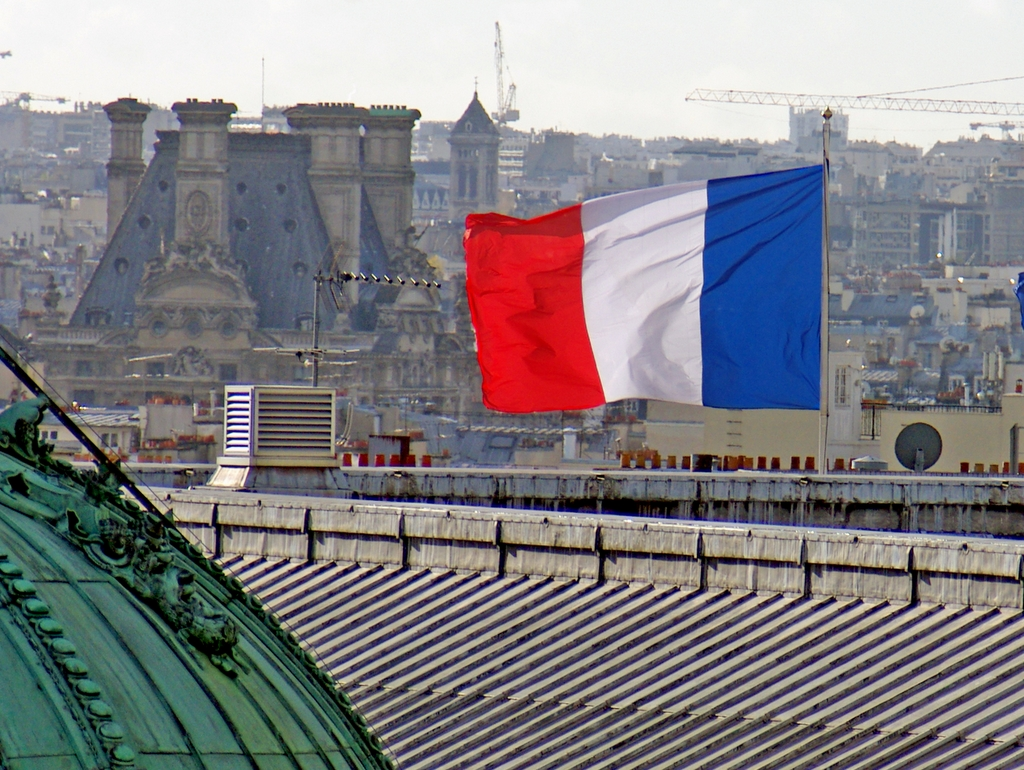 Drapeau tricolore flottant au-dessus des toits de Paris © French Moments